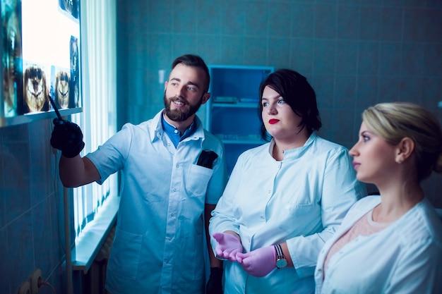 Zahnarztklinik. eine gruppe professioneller ärzte bespricht im büro die zahnärztliche behandlung auf röntgenstrahlen. moderne medizinische ausbildung.