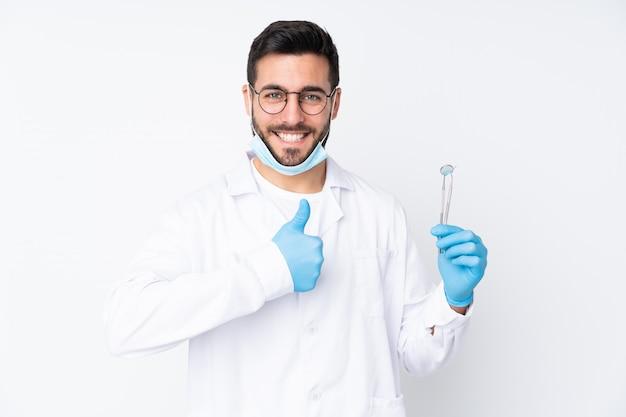 Zahnarztmann, der werkzeuge an der weißen wand hält und daumen hoch geste gibt