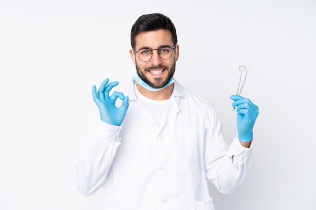 Zahnarztmann, der werkzeuge auf weißer wand hält, die ein ok-zeichen mit fingern zeigt