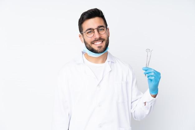 Zahnarztmann, der werkzeuge auf weißer wand hält