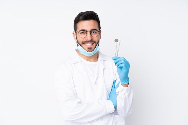 Zahnarztmann, der werkzeuge hält, die auf lachenden weißen wand lokalisiert werden