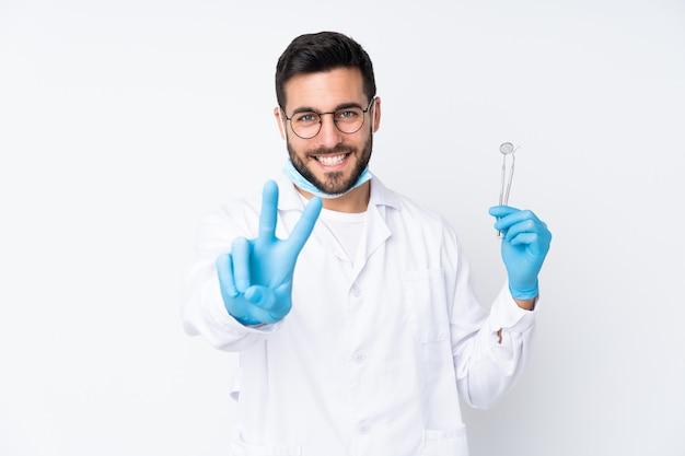 Zahnarztmann, der werkzeuge lokalisiert auf weißem wandlächeln und siegeszeichen zeigend hält