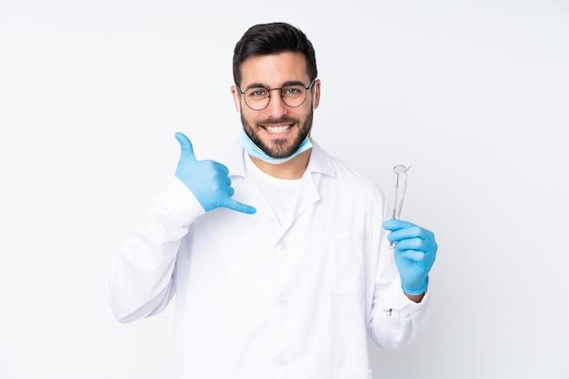 Zahnarztmann, der werkzeuge lokalisiert auf weißer wand hält, die telefongeste macht