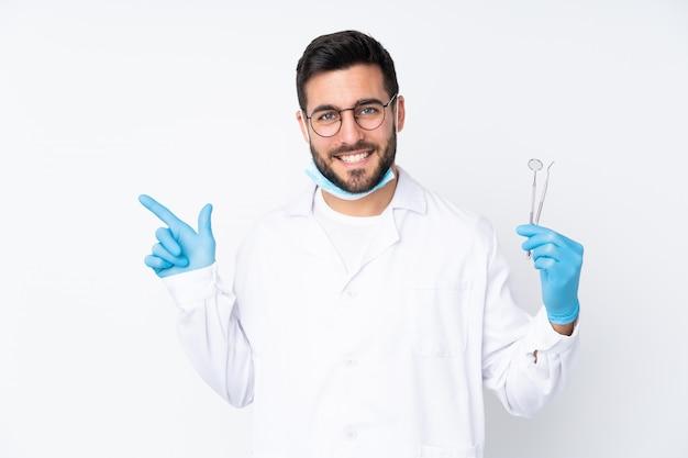 Zahnarztmann, der werkzeuge lokalisiert auf weißer wand zeigt, zeigt finger zur seite