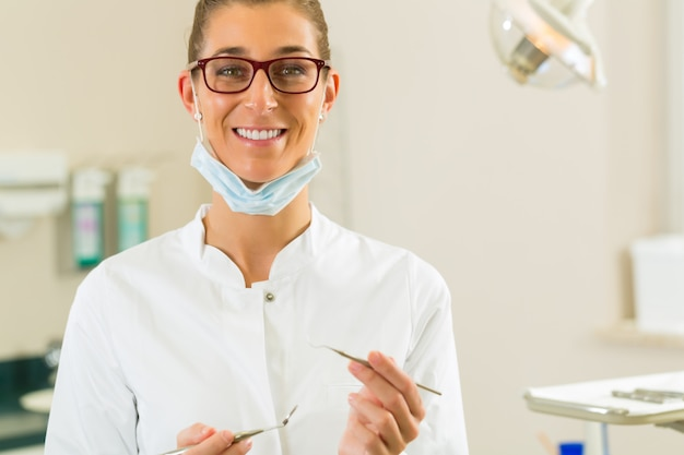 Zahnarztpraxis hält einen spiegel und bohrer, sie schaut auf den betrachter