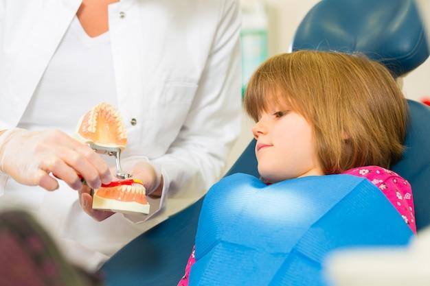 Zahnarztpraxis hält zahnersatz und erklärt einem kinderpatienten mit einer zahnbürste