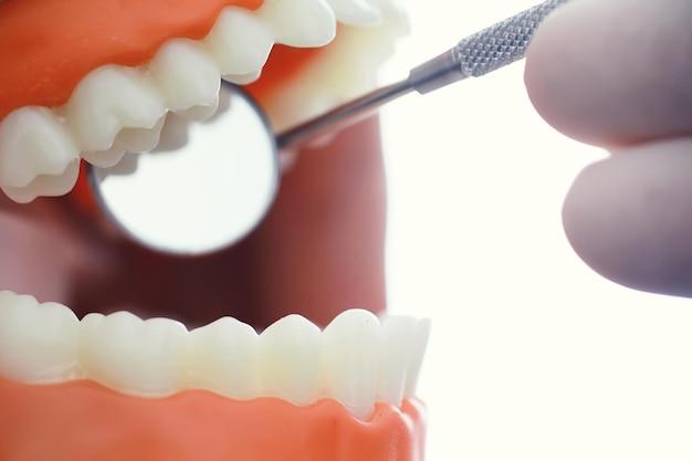 Zahnarztpraxis. zahnarzt untersucht die mundhöhle vor der behandlung. der arzt zeigt einen behandlungsverlauf. kieferbehandlung bei karies. implantation und installation von veneers.