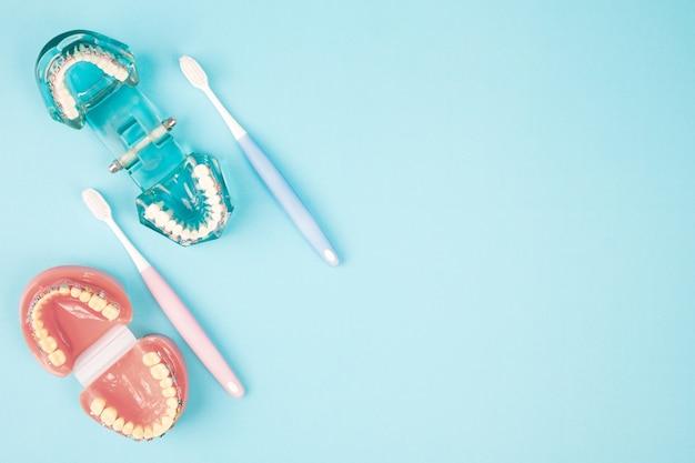 Zahnarztwerkzeuge und -kieferorthopädie auf dem blauen hintergrund, flache lage, draufsicht.