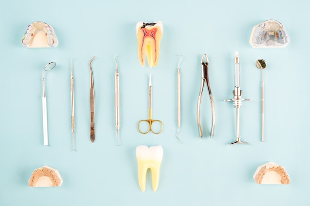 Zahnarztwerkzeuge und -prothetic auf farbhintergrund, flache lage, draufsicht.