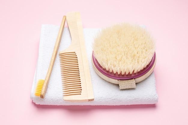 Zahnbürste, kamm und bürste aus öko-holz für trockenmassage auf rosa