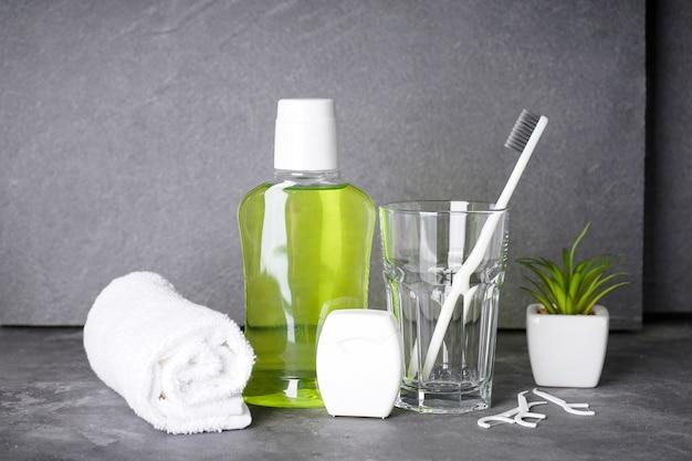Zahnbürste, mundwasser, zahnseide und handtuch auf grau
