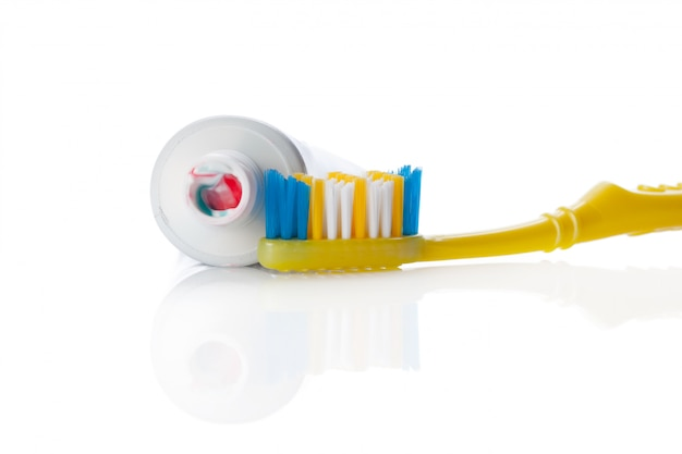 Zahnbürste und gefäß mit der paste getrennt auf weiß