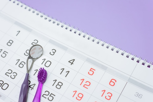 Zahnbürste und zahnärztliches instrument auf einem kalender