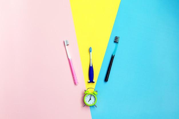 Zahnbürsten auf gelb, blau und pink. zähne putzen. schönheit und gesundheit. gesunde zähne.