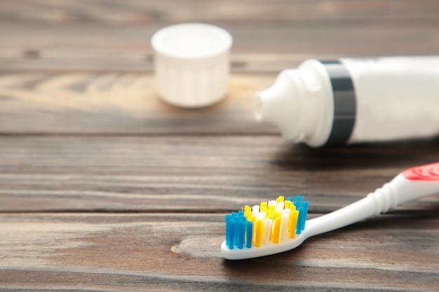 Zahnbürsten aus glas mit zahnpastatube auf braunem holz