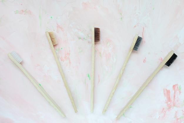 Zahnbürsten aus natürlichem holzbambus. kunststofffreies und abfallfreies konzept. draufsicht, rosa hintergrund