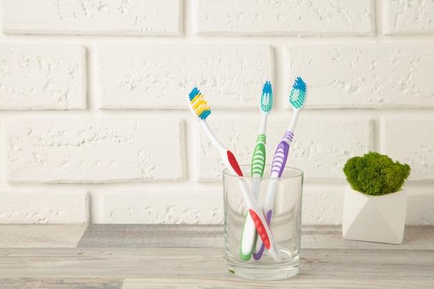 Zahnbürsten im glas auf hellem hintergrund