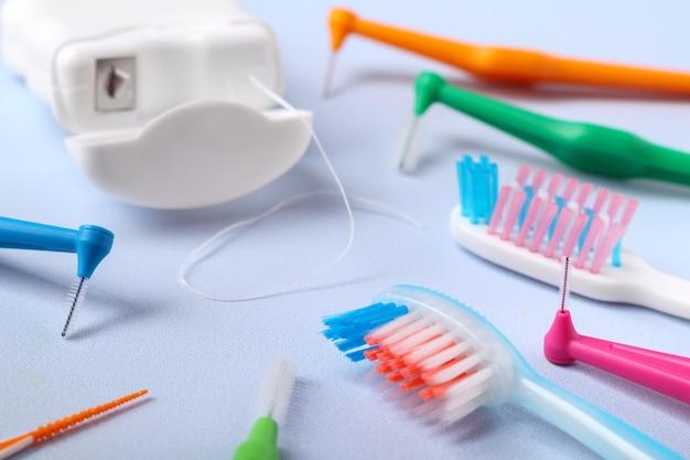 Zahnbürsten, zahnseide und interdentalzahnbürsten auf blauem hintergrund, geringe schärfentiefe. zahnärztliches und kieferorthopädisches konzept.
