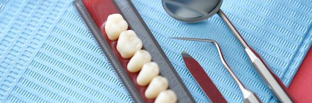 Zahnersatz und zahnärztliche instrumente liegen auf tischnahaufnahme