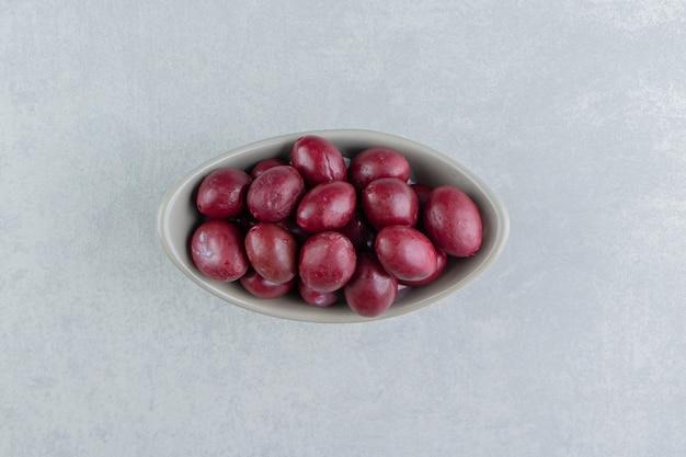Zahnfrische eingelegte pflaumen auf der marmoroberfläche