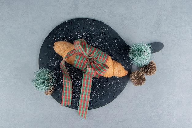 Zahnhafte croissants auf der blauen tafel auf dem marmorhintergrund. hochwertiges foto