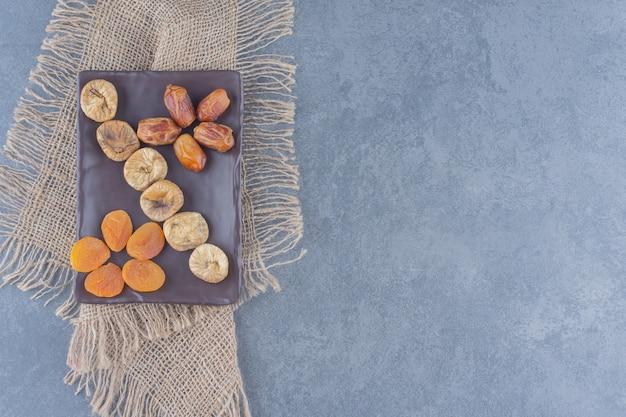 Zahnhafte getrocknete früchte auf dem brett, auf dem untersetzer, auf dem marmorhintergrund.