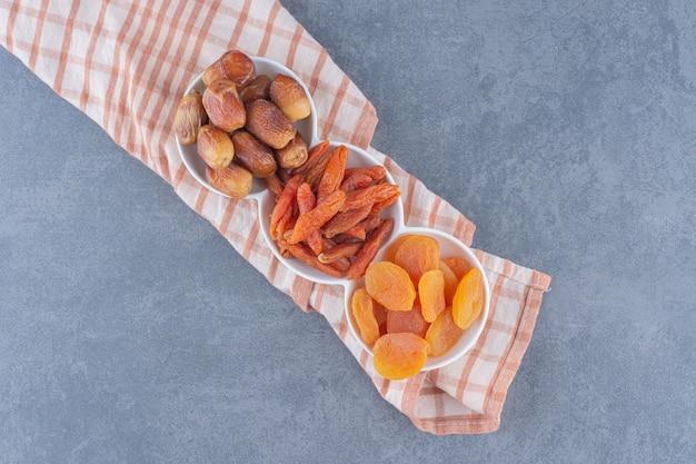 Zahnhafte getrocknete früchte auf dem handtuch, auf dem marmorhintergrund.