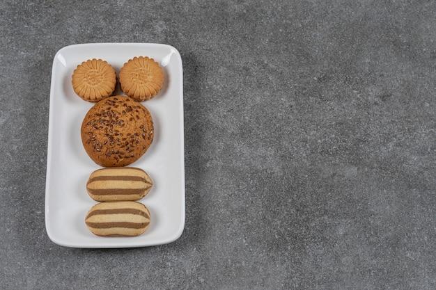Zahnhafte kekse auf dem teller auf der marmoroberfläche