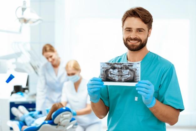 Zahnheilkunde hält eine röntgenaufnahme des kiefers im klinikraum