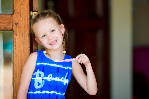 Zahnhygiene. entzückendes kleines lächelnmädchen, das ihre zähne putzt