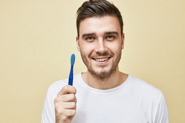 Zahnhygiene und gesundes mundbereichskonzept. porträt des attraktiven glücklichen jungen mannes, der morgenroutine tut, die lokal mit zahnbürste aufwirft, zähne vor dem schlafengehen reinigt und mit lächeln schaut