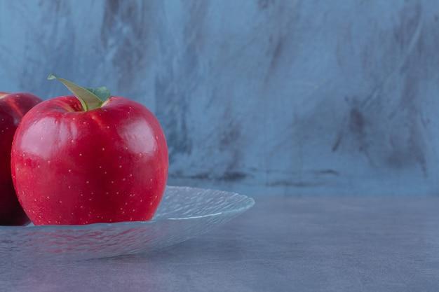 Zahnige äpfel auf einer glasplatte auf marmortisch.