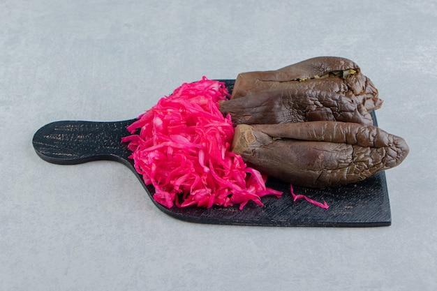 Zahnige aubergine und eingelegter rotkohl auf dem schneidebrett auf der marmoroberfläche
