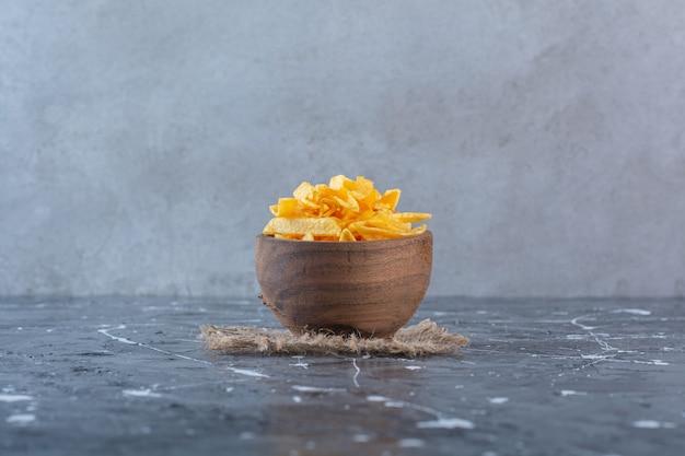 Zahnige kartoffelchips in holzschale auf textur, auf der marmoroberfläche