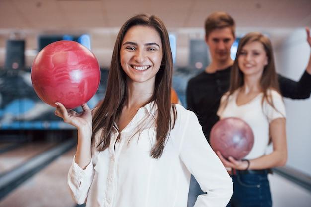 Zahnlächeln. junge fröhliche freunde haben an ihren wochenenden spaß im bowlingclub