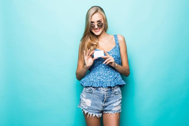 Zahnlächelnde junge frau in der sonnenbrille halten kreditkarte auf blauem hintergrund.