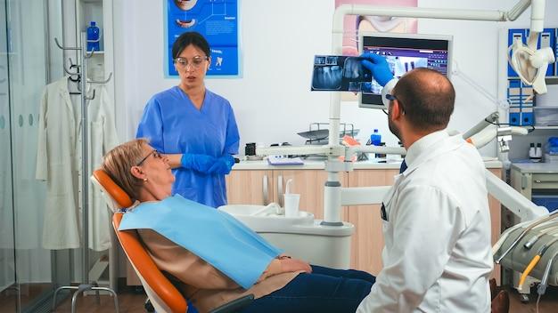 Zahnmediziner bespricht mit dem patienten einen plan für die wiederherstellung und rehabilitation von zahnersatz mit blick auf röntgenstrahlen. zahnarzt bittet um zahnärztliches röntgen während der patientenberatung, krankenschwester arbeitet am computer