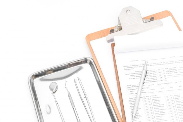 Zahnmedizinische werkzeuge, ausrüstung und zahnmedizinische diagramm auf weißem hintergrund