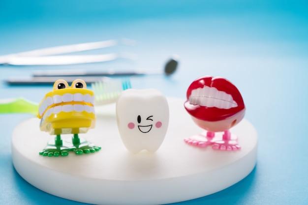 Zahnmedizinische werkzeuge und lächelnzähne modellieren auf blau.