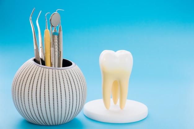 Zahnmedizinische werkzeuge und zahnanatomie auf blauem hintergrund.