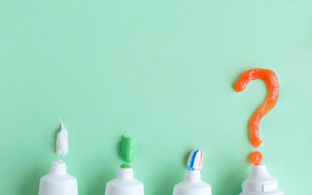 Zahnpasta liegt auf grün und einem fragezeichen.