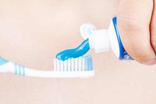 Zahnpasta wird auf die zahnbürste aufgetragen, konzept: zähneputzen