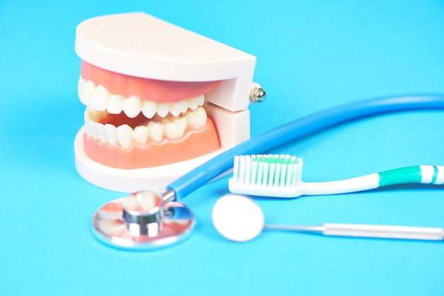 Zahnpflegezahnarztwerkzeuge mit gebisszahnheilkundeinstrumenten und zahnpflege- und -ausrüstungsüberprüfung mit zahnmodell und mundspiegelmundgesundheit