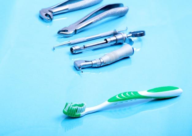 Zahnpflegezahnbürste mit zahnarztwerkzeugen auf spiegelhintergrund.