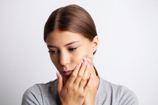 Zahnprobleme, eine attraktive frau hat schmerzhafte zahnschmerzen