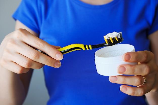 Zahnpulver für die zahnaufhellung auf der zahnbürste in den händen des mädchens.