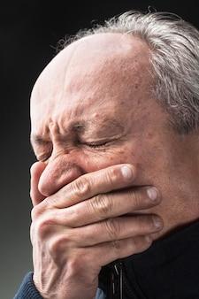 Zahnschmerzen. älterer mann mit von hand geschlossenem gesicht