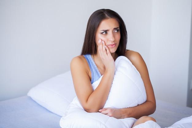 Zahnschmerzen. schöne frau, die unter schmerzlichen zahnschmerzen leidet
