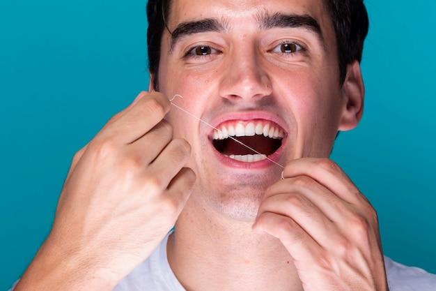 Zahnseide des gutaussehenden mannes der nahaufnahme