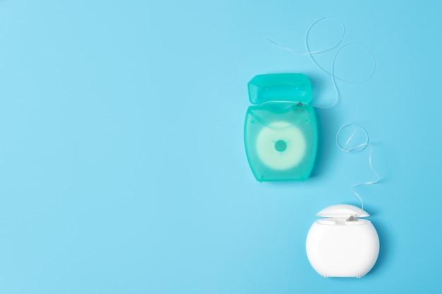 Zahnseidenbehälter auf blauem hintergrund. tägliche mundhygiene, zahnpflege und gesundheit. reinigungsprodukte für den mund, kopierraum. zahnpflegekonzept.